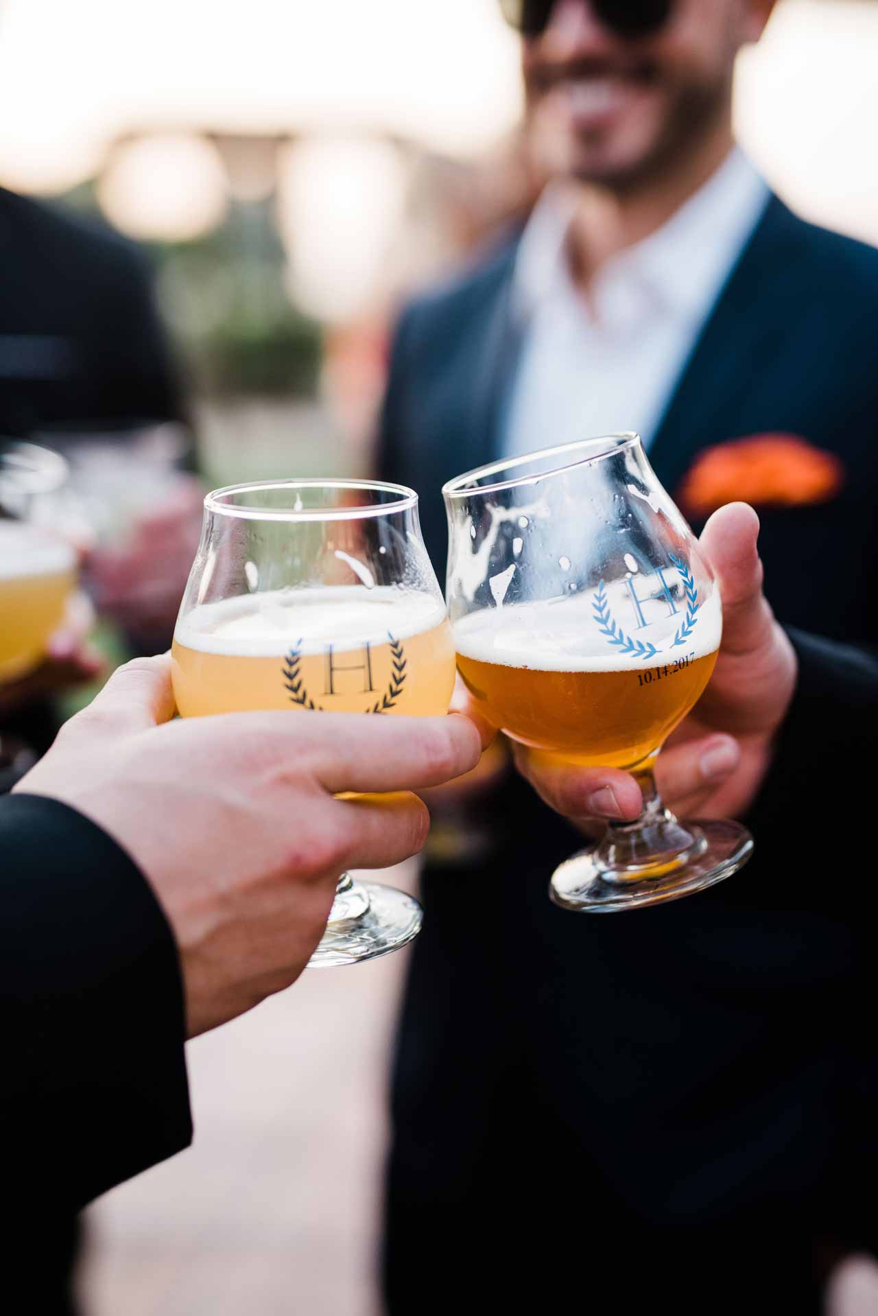 Two groomsmen raising a pint and toasting with custom beer glasses at a wedding
