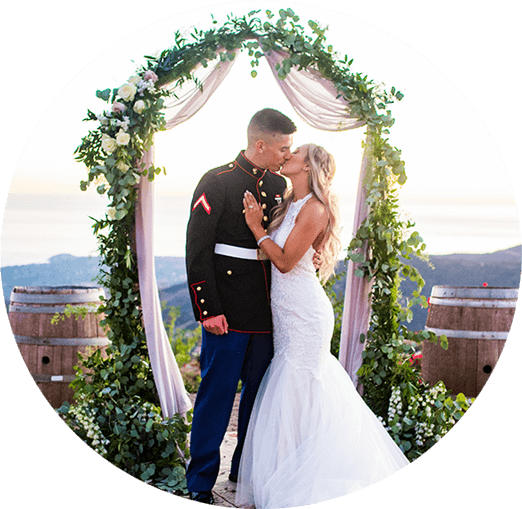 Military groom marrying his blond bride outside with an archway of flowers.